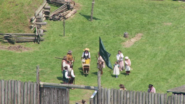 ms ts aerial view over women and children with wheelbarrow walking through gate at fort randolph reenactment / point pleasant, west virginia, united states - american revolution stock videos & royalty-free footage