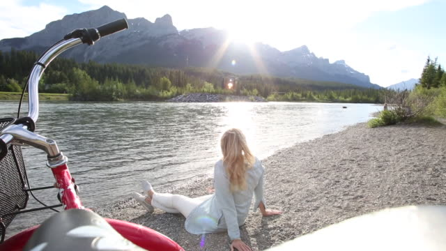 view past bike handlebars to woman relaxing on river beach, mountains - legs crossed at ankle stock videos and b-roll footage
