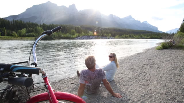 View past bikes to couple relaxing on river beach, mountains