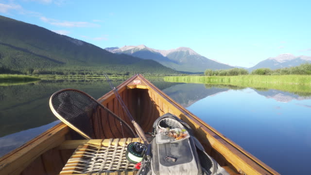 view past bow of wooden canoe with fishing gear, mountain lake - fishing rod stock videos & royalty-free footage