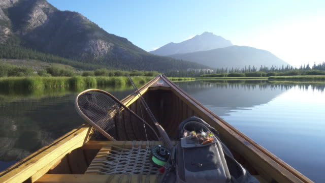 View past bow of wooden canoe with fishing gear, mountain lake
