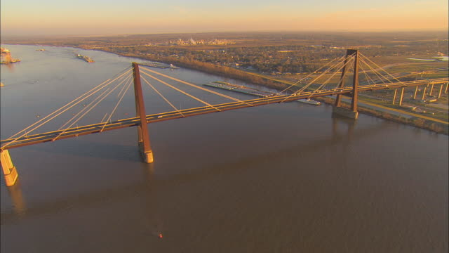 AERIAL WS View past Hale Boggs Memorial Bridge and along levee on Mississippi River / Destrehan, Louisiana, USA