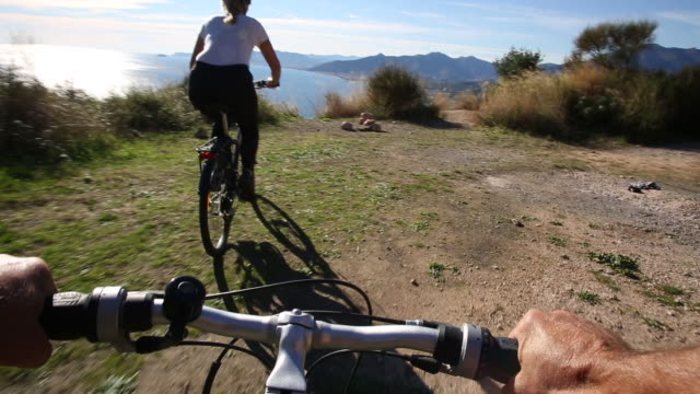 view past handlebars to woman bicycling, then out to sea - handlebar stock videos & royalty-free footage