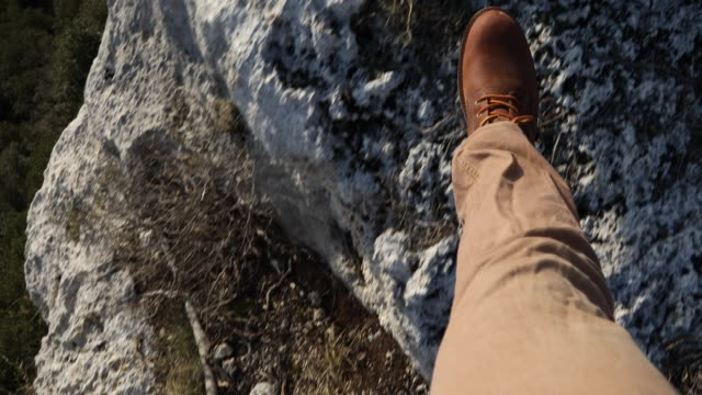 view past hiker's feet walking along rock ridge - human leg stock videos & royalty-free footage