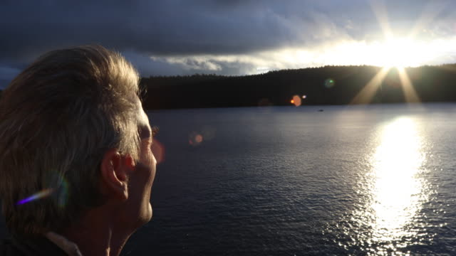 view past man's face to sun rising over ocean - canada stock videos & royalty-free footage
