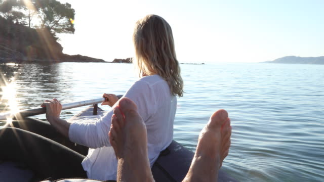 view past man's feet as woman paddles inflatable kayak, sunrise - kayak video stock e b–roll