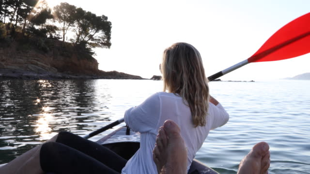 View past man's feet as woman paddles inflatable kayak, sunrise