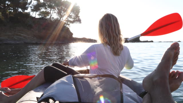 view past man's feet as woman paddles inflatable kayak, sunrise - カタルーニャ州点の映像素材/bロール