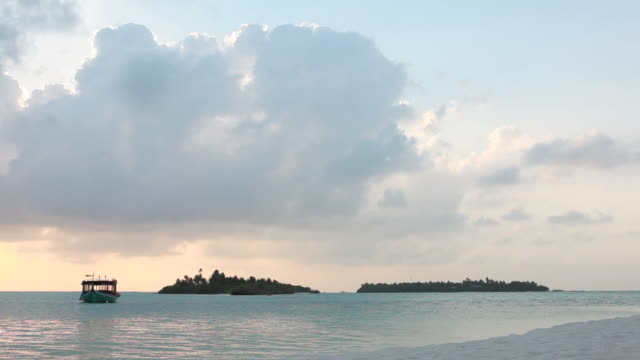 View past white sand beach to anchored boat, sunset