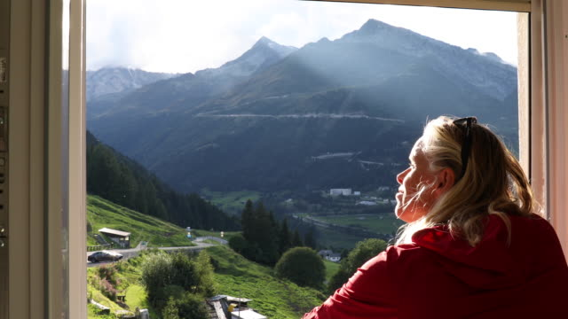 vídeos de stock e filmes b-roll de view past woman's face looking out window to mountains - janela aberta