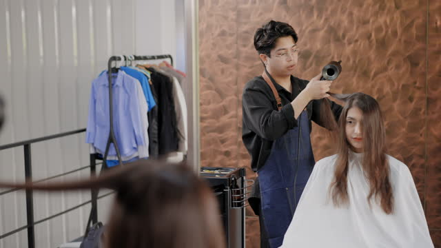 vidéos et rushes de voir le reflet sur un miroir: jeune homme asiatique barber en tant que coiffeur faisant service cheveux raides de belles cheveux bruns de la femme caucasienne en utilisant un sèche-cheveux, peigne à cheveux à la boutique de salon, concept de la vie d' - brown hair