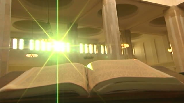 view the sun's rays flaring over an open qoran inside a mosque. - architecture stock videos & royalty-free footage