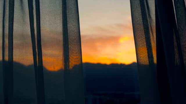 vídeos de stock e filmes b-roll de view the sunset through curtains - curtain