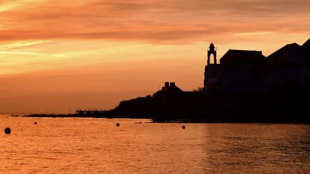 view the wellington clock tower during sunrise, swanage, dorset uk - brandungsfischen stock-videos und b-roll-filmmaterial