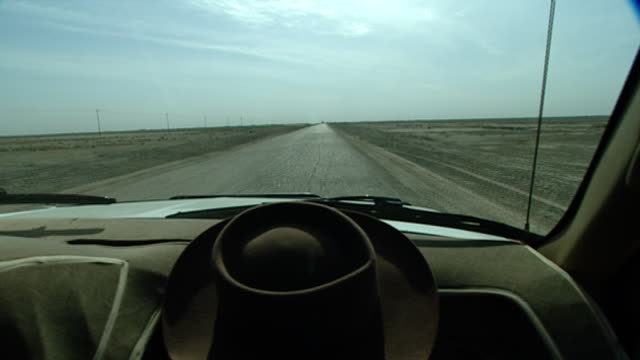 vidéos et rushes de view through a car windscreen of a long and lonely road stretching out into the iraqi desert south of baghdad towards warka. - driving plate image animée