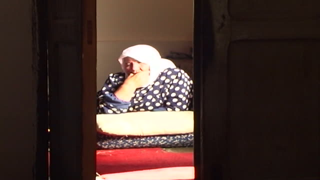 stockvideo's en b-roll-footage met view through a dark open doorway of a sunlit pensive old shia woman sitting on the floor leaning on a cushion - stippen