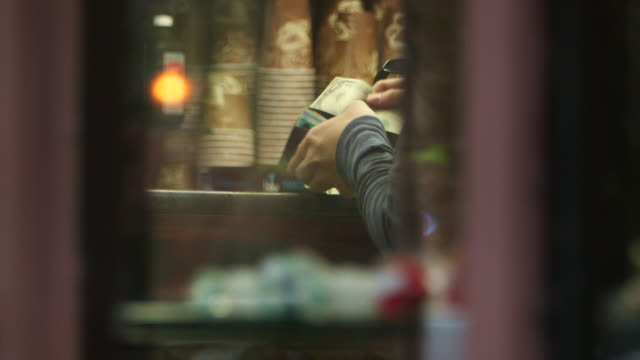vidéos et rushes de view through a shop window of a person paying cash for goods in the east village, ny - billet de banque