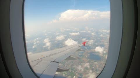 stockvideo's en b-roll-footage met uitzicht door een vliegtuig venster op de hemel en wolken. - window