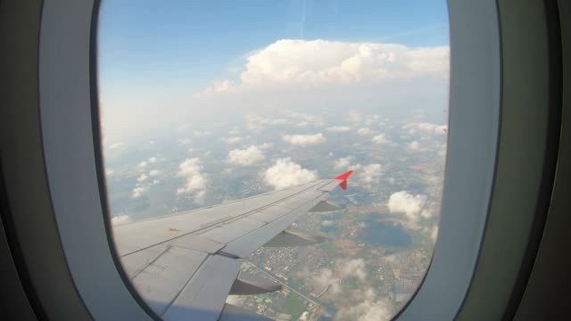 view through an airplane window on the sky and clouds. - aircraft wing stock videos & royalty-free footage