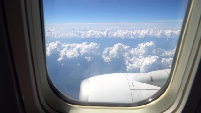 visa genom ett flygplansfönster på himlen och moln - aircraft point of view bildbanksvideor och videomaterial från bakom kulisserna