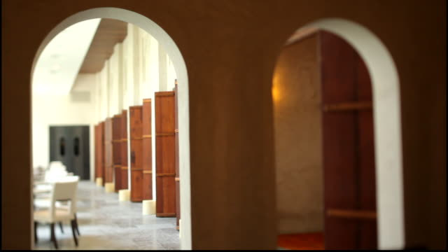 view through an arch to a modern dining room in the restored buzaboon house part of the shaikh ebrahim center for culture, showcasing traditional... - dining room stock videos & royalty-free footage