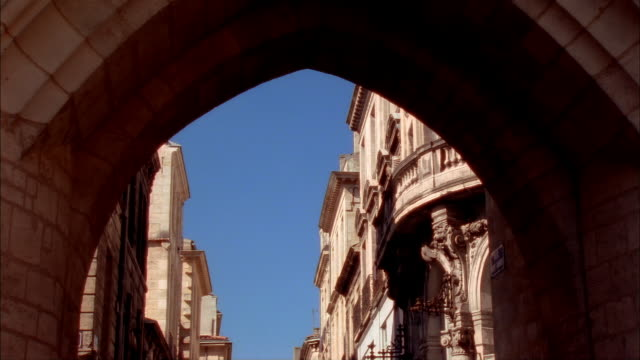 view through archway of la grosse cloche of buildings on clear day / bordeaux, france - 大時計点の映像素材/bロール
