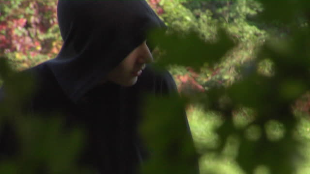 SHAKY CU TD TU View through bushes of two hooded boys exchanging package in park / London, England