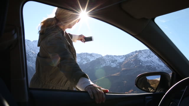 view through car window as woman takes pic with smart phone - hood clothing stock videos and b-roll footage