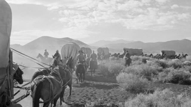 WS View through desert with mountains and wagon train enters