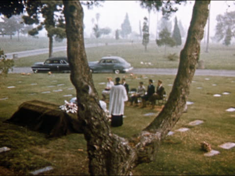 1955 view through forked tree trunk of small christian funeral ceremony on foggy day / usa - cemetery stock videos & royalty-free footage