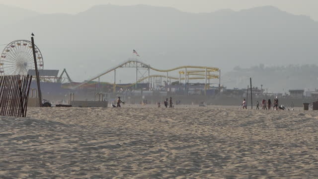 view through heat distortion people walking by a large roller coaster in the background - distorted stock videos & royalty-free footage
