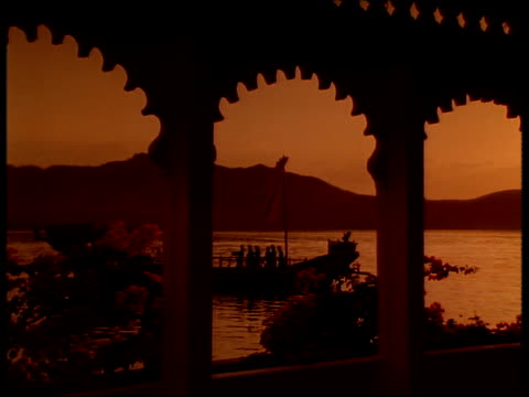 vidéos et rushes de view through moorish arch of men rowing royal boat past lake palace at dusk silhouettes of hills in distance under amber sky udaipur. - palace