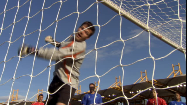 ms view through net of goal being scored in soccer game/ sheffield, england - turno sportivo video stock e b–roll