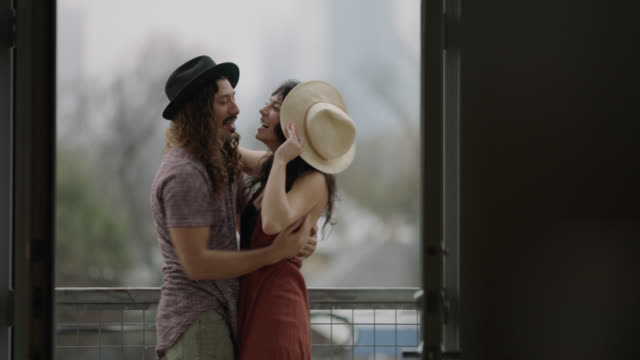 view through open door as hip young couple embrace and kiss and playfully swap hats on city balcony. - passione video stock e b–roll
