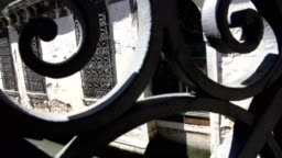 view through the openwork, forged bridge to the old building, standing on the water of the canal, with forged old bars on the windows
