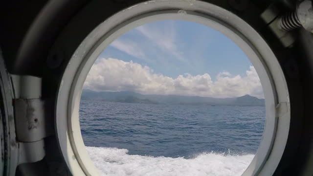 POV view through the porthole on a motor boat sailing on the blue sea. - Slow Motion