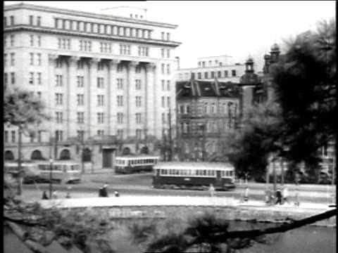 view through tree branches of large white buildings / cars and trolleys moving on street in front of white building / cars driving past building / - trolleybus stock-videos und b-roll-filmmaterial