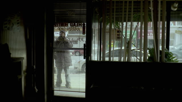 ms view through window blinds of man closing roller door of barber shop, brooklyn, new york city, new york state, usa - tapparella video stock e b–roll