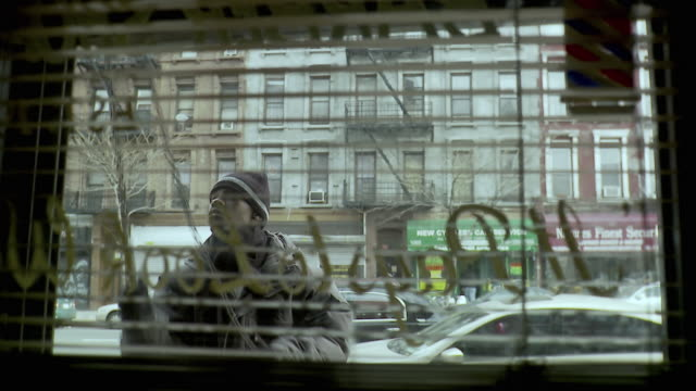 vídeos de stock, filmes e b-roll de ms view through window blinds of man closing roller door of shop, brooklyn, new york city, new york state, usa - persiana