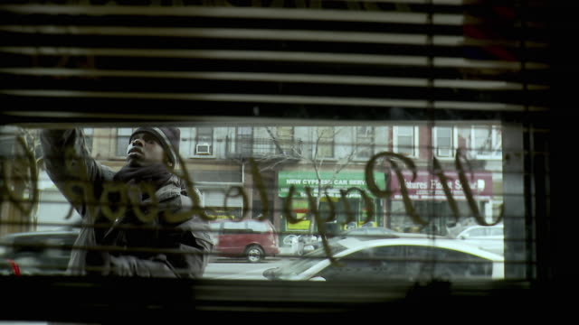 MS View through window blinds of man opening roller door of barber shop, Brooklyn, New York City, New York State, USA