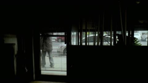 vídeos y material grabado en eventos de stock de ms view through window blinds of man opening roller door of barber shop, brooklyn, new york city, new york state, usa - abierto