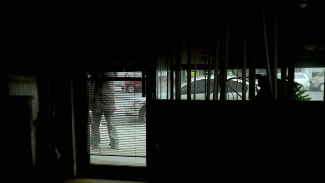 ms view through window blinds of man opening roller door of barber shop, brooklyn, new york city, new york state, usa - blinds stock videos & royalty-free footage