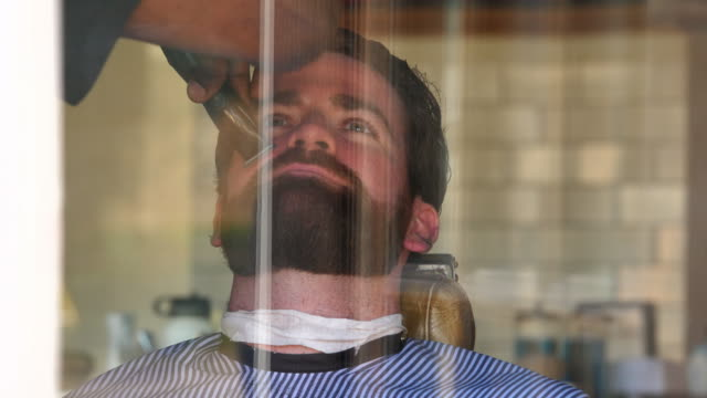 vídeos de stock, filmes e b-roll de cu view through window of barber trimming mans beard in barber shop - controlo de qualidade