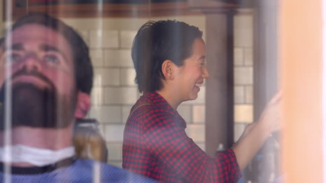 ms view through window of female barber cutting hair in busy barber shop - gingham stock videos & royalty-free footage
