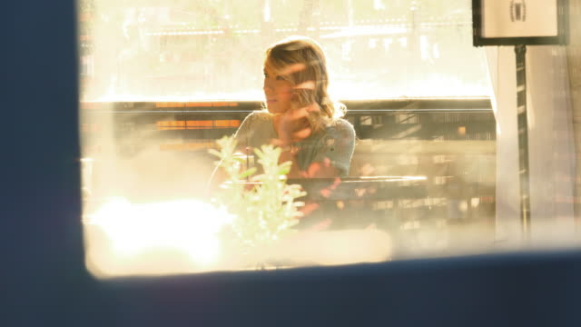 MS View through window of smiling woman enjoying drink in bar