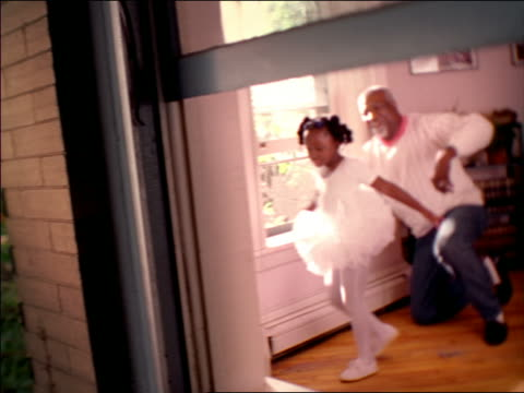 view through window of soft focus senior black man watching young black girl in tutu spinning - soft focus stock videos & royalty-free footage