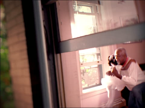 vídeos de stock, filmes e b-roll de view through window of soft focus young black girl in ballet tutu hugging kneeling senior black man - foco difuso
