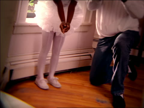 CANTED SOFT FOCUS view through window senior man instructs Black girl in tutu spinning
