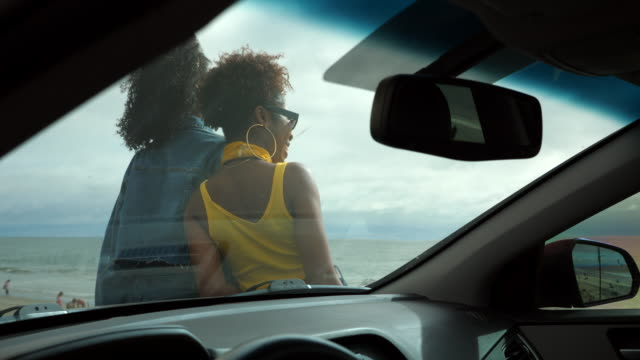 ms view through windshield of female friends leaning on hood of car while parked at beach - bonnet stock videos & royalty-free footage