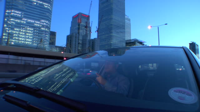 MS View through windshield of man driving through Canary Wharf at dusk/ London, England
